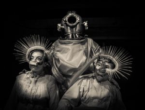 [Warm toned Black and white photo of 3 figures in surreal costumes. The central figure supports the two flanking figures. All are seated. The central figure wears a 19th century diving bell and a 20th century space suit. The flanking figures wear 19th century linen night shirts and strange breathing masks over their noses. Many spines protrude from each breathing mask, part medical device part undersea creature.]
